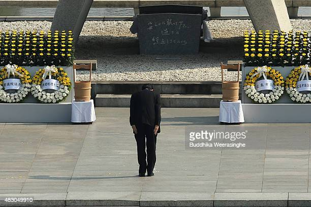 Japan's Prime Minister Shinzo Abe bows in front of the cenotaph dedicated to the victims of the atomic bombingat the Hiroshima Peace Memorial Park on...