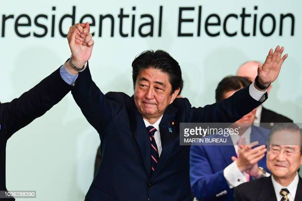TOPSHOT Japan's Prime Minister Shinzo Abe celebrates after the ruling liberal Democratic Party leadership election at the party's headquarters in...