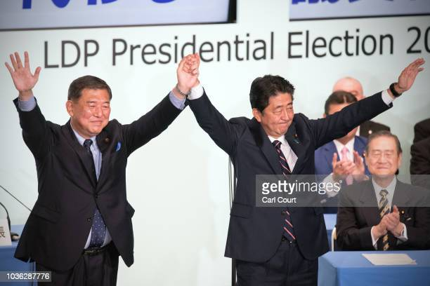 Japan's Prime Minister Shinzo Abe celebrates with Shigeru Ishiba the former defence minister who ran against him after winning the Liberal Democratic...