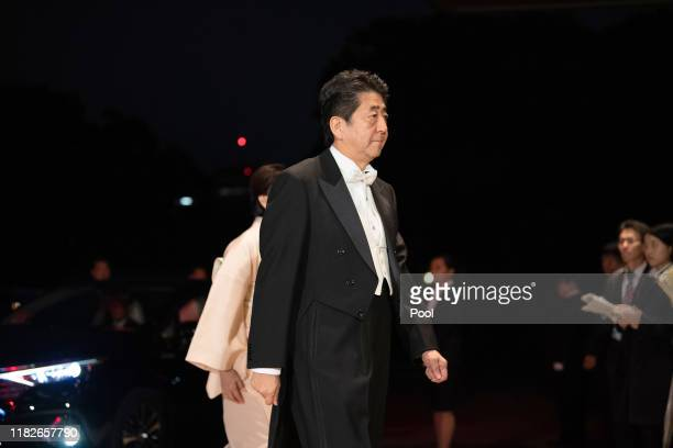Japan's Prime Minister Shinzo Abe, center, and his wife Akie Abe, behind arrive at the Imperial Palace for the Court Banquets after the Ceremony of...