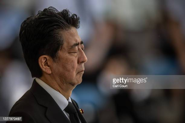 Japan's Prime Minister Shinzo Abe closes his eyes as he observes a moment of silence during the 75th anniversary of the Nagasaki atomic bombing on...