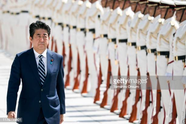 Japan's Prime Minister Shinzo Abe inspects an honor guard ahead of a Self Defense Forces senior officers' meeting at the Ministry of Defense on...