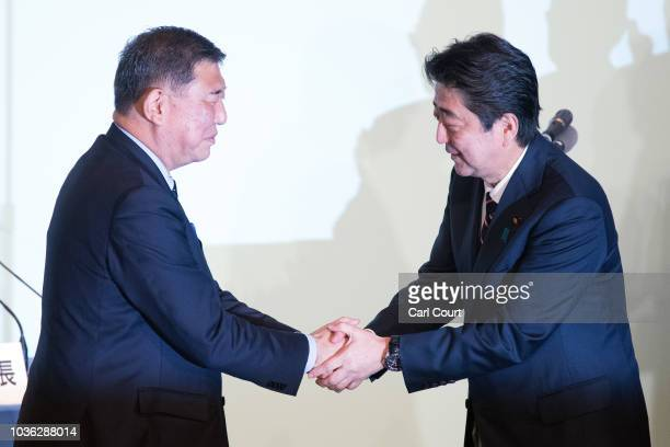 Japan's Prime Minister Shinzo Abe is congratulated by Shigeru Ishiba the former defence minister who ran against him after winning the Liberal...
