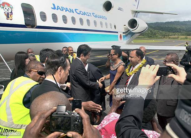 Japan's Prime Minister Shinzo Abe is greeted by Papua New Guinea Foreign Minister Rimbink Paton after disembarking from his plane during a visit to...