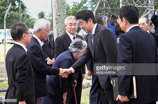 Japan's Prime Minister Shinzo Abe is greeted during his visit to Wewak in Papua New Guinea on July 11 2014 Abe is visiting New Zealand Australia and...