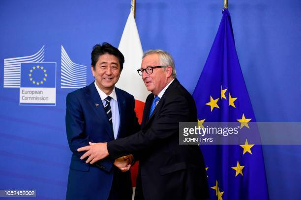 Japan's Prime Minister Shinzo Abe is welcomed by European Commission President JeanClaude Juncker as he arrives at the European Council in Brussels...
