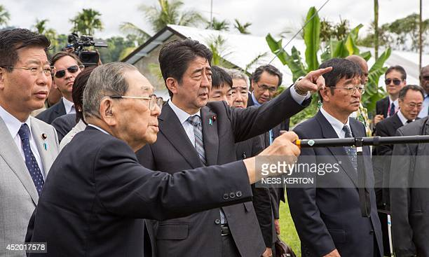 Japan's Prime Minister Shinzo Abe listens to 99yearold Mario Morie at a peace park in Wewak in Papua New Guinea on July 11 2014 Abe is visiting New...