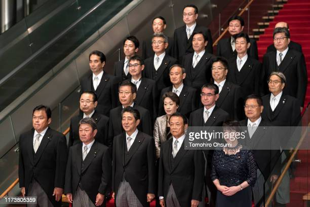 Japan's Prime Minister Shinzo Abe poses for a group photograph with his Cabinet members at the prime minister's official residence on September 11...