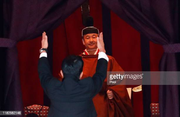 "Japan's Prime Minister Shinzo Abe raises his hands as he shouts ""banzai"" or cheers in front of Emperor Naruhito during a ceremony to proclaim Emperor..."