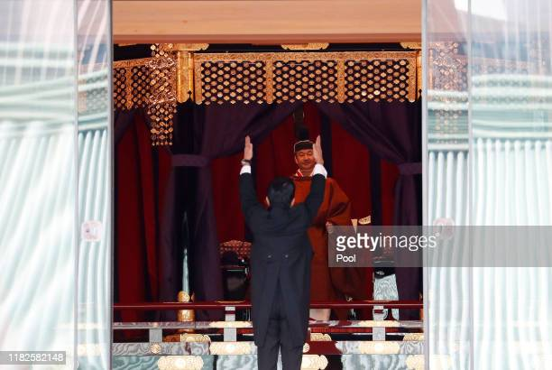 """Japan's Prime Minister Shinzo Abe raises his hands as he shouts """"banzai"""" or cheers in front of Emperor Naruhito during a ceremony to proclaim Emperor..."""