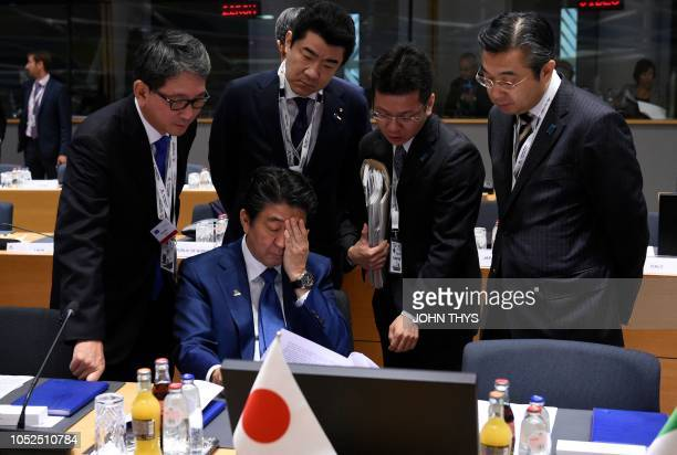 TOPSHOT Japan's Prime Minister Shinzo Abe reacts as he studies documents with officials ahead of a Asia Europe Meeting at the European Council in...