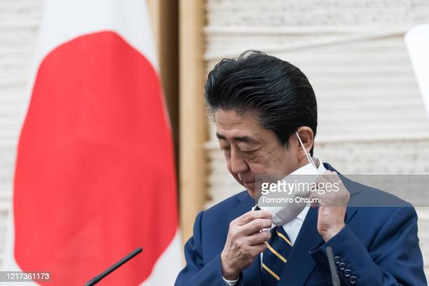 Japan's Prime Minister Shinzo Abe removes his face mask during a press conference at the prime minister's official residence on April 07, 2020 in...