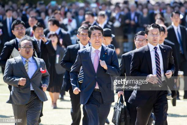 Japan's Prime Minister Shinzo Abe runs during the cherry blossom viewing party at the Shinjuku Gyoen National Garden on April 13 2019 in Tokyo Japan