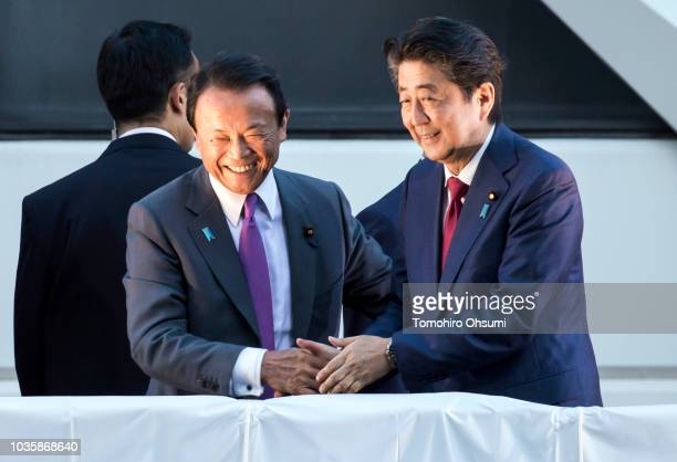 Japan's Prime Minister Shinzo Abe shakes hands with Deputy Prime Minister and Finance Minister Taro Aso during a campaign rally for the Liberal...