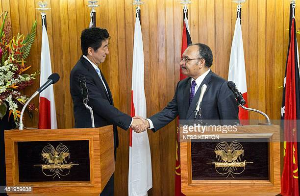 Japan's Prime Minister Shinzo Abe shakes hands with Papua New Guinea Prime Minister Peter O'Neil in Port Moresby on July 10 2014 Abe is visiting New...