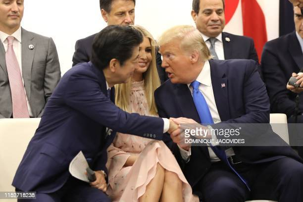 Japan's Prime Minister Shinzo Abe shakes hands with US President Donald Trump as Advisor to the US President Ivanka Trump sit between them during an...