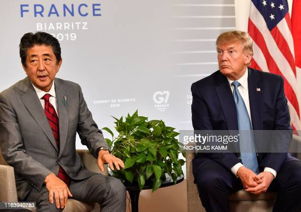 Japan's Prime Minister Shinzo Abe sits with US President Donald Trump during a bilateral meeting on the sidelines of the G7 summit in Biarritz...