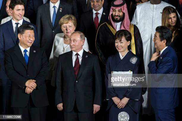 Japan's Prime Minister Shinzo Abe speaks to China's President Xi Jinping as Russia's President Vladimir Putin and Japan's first lady Akie Abe look on...