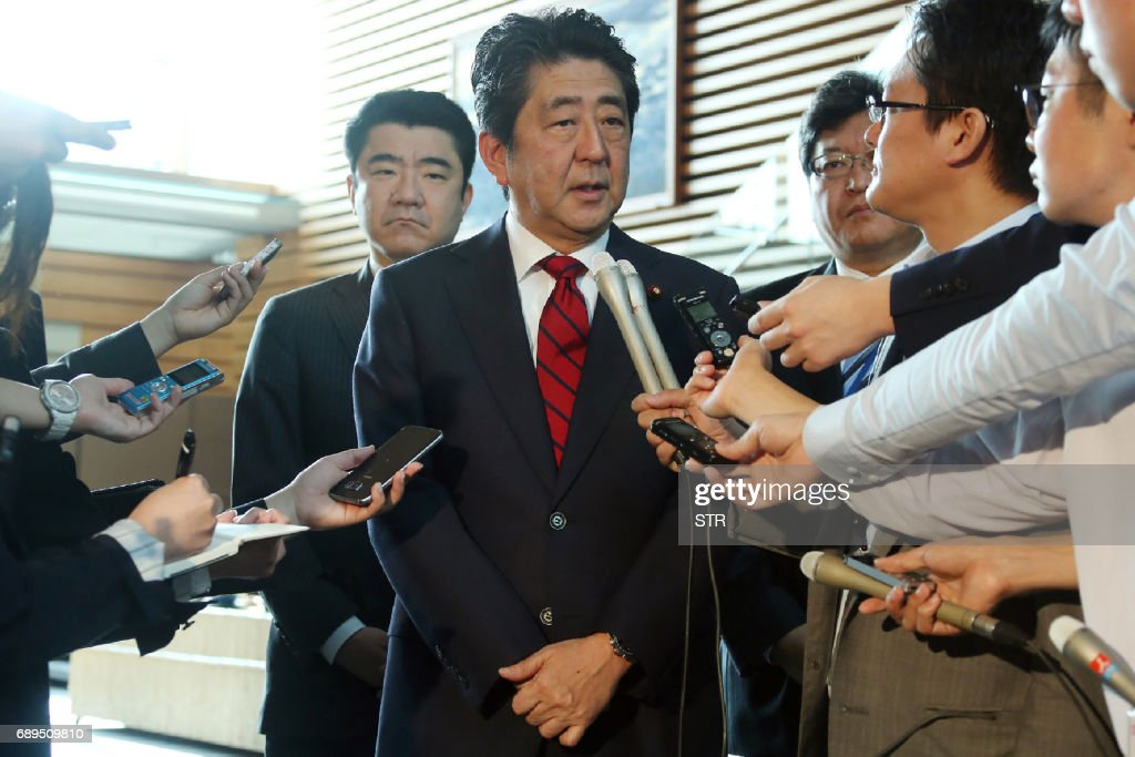 Japan's Prime Minister Shinzo Abe (C) speaks to reporters at his official residence in Tokyo on May 29, 2017. North Korea on May 29 test-fired a ballistic missile, the latest in a series of launches that have ratcheted up tensions over its quest to develop weapons capable of hitting the United States. Abe swiftly condemned Monday's launch and vowed 'concrete action' with the US. / AFP PHOTO / JIJI PRESS / STR / Japan OUT
