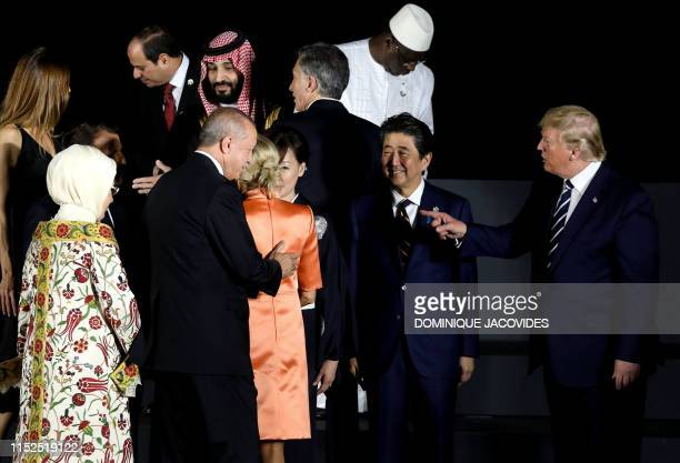 Japan's Prime Minister Shinzo Abe stands next to US President Donald Trump gesturing toward Turkey's president Recep Tayyip Erdogan and his wife...