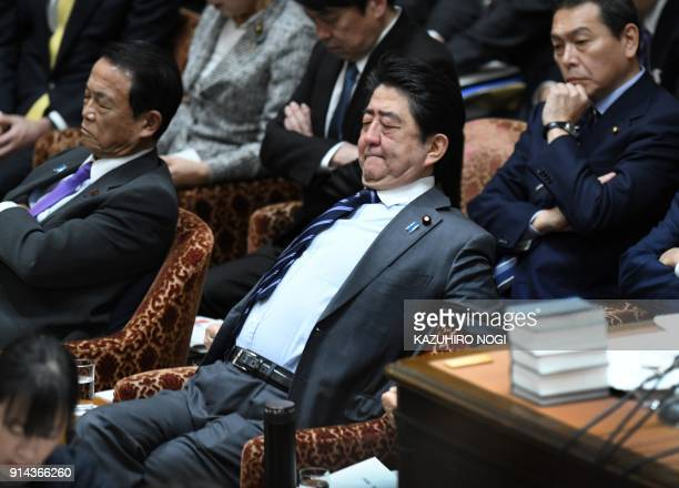 TOPSHOT Japan's Prime Minister Shinzo Abe stretches in his chair during a session of the House of Representatives Budget Committee at parliament in...