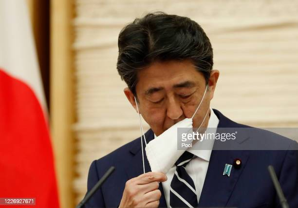 Japan's Prime Minister Shinzo Abe takes off his protective as he begins his news conference on May 25, 2020 in Tokyo, Japan. Prime Minister Abe said...