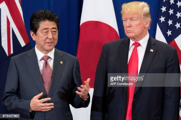 Japan's Prime Minister Shinzo Abe talks to US President Donald Trump during the opening ceremony of the 31st Association of South East Asian Nations...