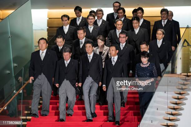 Japan's Prime Minister Shinzo Abe walks to a group photograph with his Cabinet members at the prime minister's official residence on September 11...