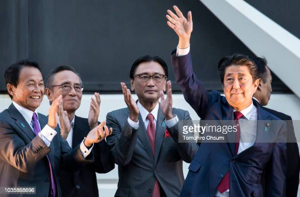 Japan's Prime Minister Shinzo Abe waves as Deputy Prime Minister and Finance Minister Taro Aso claps during a campaign rally for the Liberal...