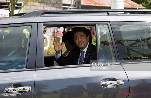 Japan's Prime Minister Shinzo Abe waves to the local during a visit to Wewak in Papua New Guinea on July 11 2014 Abe is visiting New Zealand...