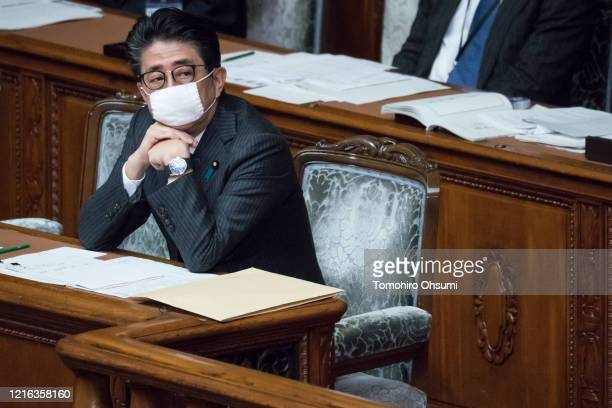 Japan's Prime Minister Shinzo Abe wearing a face mask attends an ordinary session at the upper house of Parliament on April 02 in Tokyo, Japan. Abe...