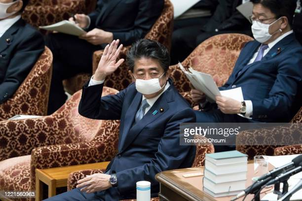 Japan's Prime Minister Shinzo Abe wearing a face mask raises his hand to answer to a question during a budget committee meeting at the lower house of...