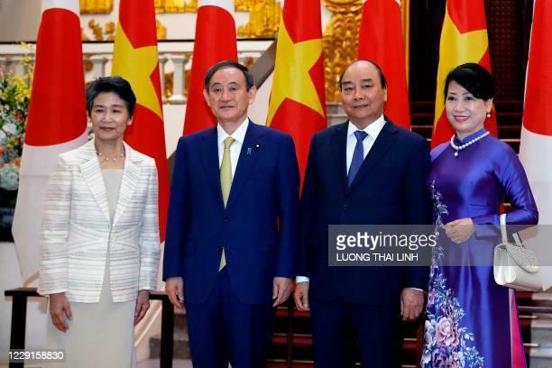Japan's Prime Minister Yoshihide Suga and his wife Mariko Suga pose for photos with Vietnam's Prime Minister Nguyen Xuan Phuc and his wife Tran Thi...