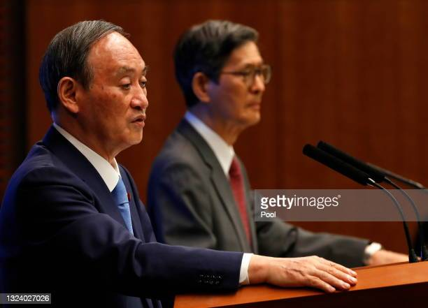 Japan's Prime Minister Yoshihide Suga and Shigeru Omi, President of the Japan Community Health Care Organization, attend a news conference on Japan's...