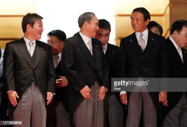 Japan's Prime Minister Yoshihide Suga exchanges smiles with Deputy Prime Minister and Finance Minister Taro Aso and Foreign Minister Toshimitsu...