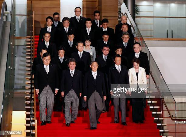 Japan's Prime Minister Yoshihide Suga leads his cabinet as they prepare for a group photograph at the prime minister's official residence on...