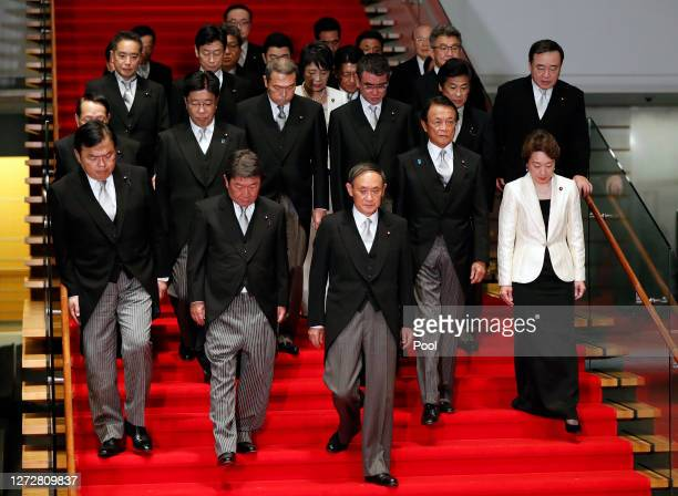 Japan's Prime Minister Yoshihide Suga leads his cabinet members as they prepare for a group photograph at the prime minister's official residence on...