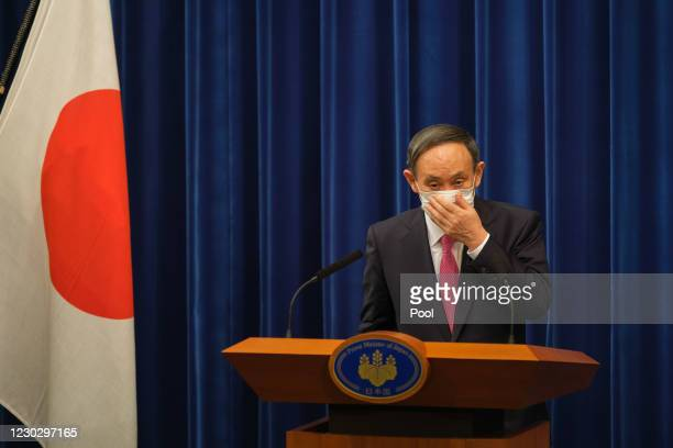 Japan's Prime Minister Yoshihide Suga puts on a face mask after a press conference on December 25, 2020 in Tokyo, Japan. Mr Suga urged people to be...