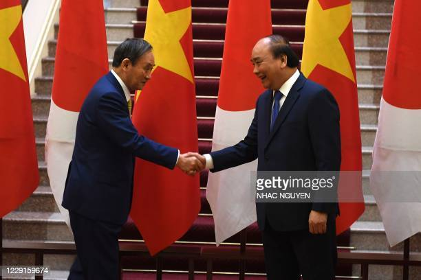 Japan's Prime Minister Yoshihide Suga shakes hands with Vietnam's Prime Minister Nguyen Xuan Phuc after witnessing an exchange of documents at the...