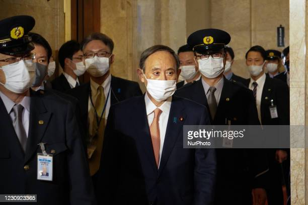 Japan's Prime Minister Yoshihide Suga walks with security guards inside the parliament building before a debate session regarding the bills to...