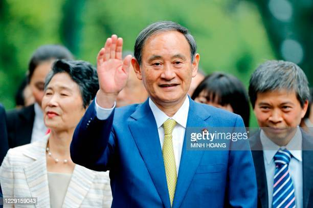Japan's Prime Minister Yoshihide Suga waves during an official visit at the Presidential Palace in Hanoi on October 19, 2020.
