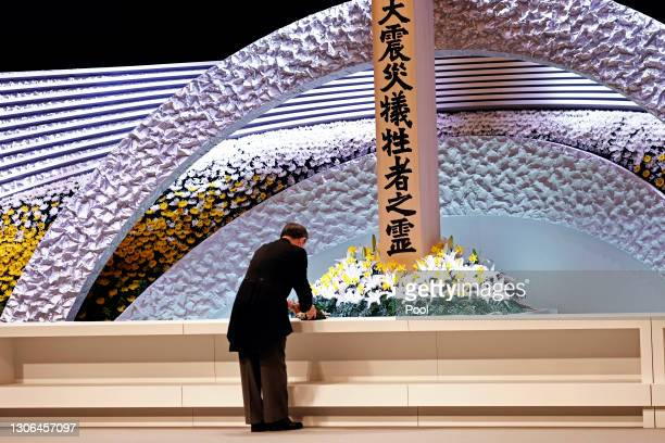 Japan's Prime Minister Yushihide Suga places some flowers in front of the altar for victims of the March 11, 2011 earthquake and tsunami at the...