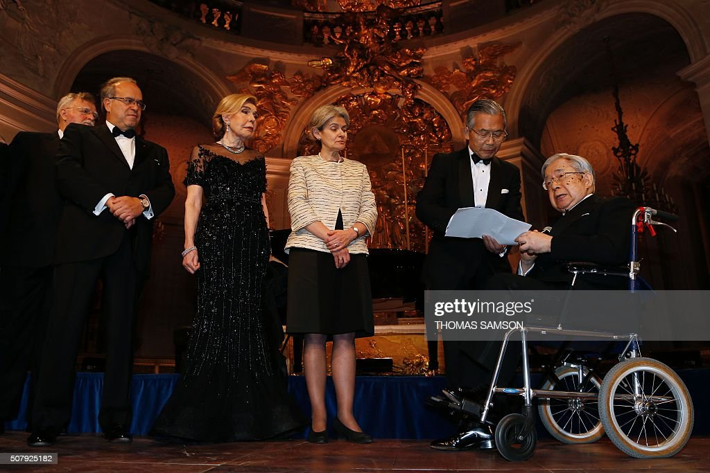 Japan's Prince Hitachi (R) is awarded the Grand Prize of the Charter of Paris against cancer on February 1, 2016, in Versailles, near Paris, as David Khayat (L), co-founder of the foundation Avec, UNESCO Ambassador Marianna Vardinoyannis (2nd L) and UNESCO exedcutive director Irina Bokova applaud look on. / AFP / THOMAS