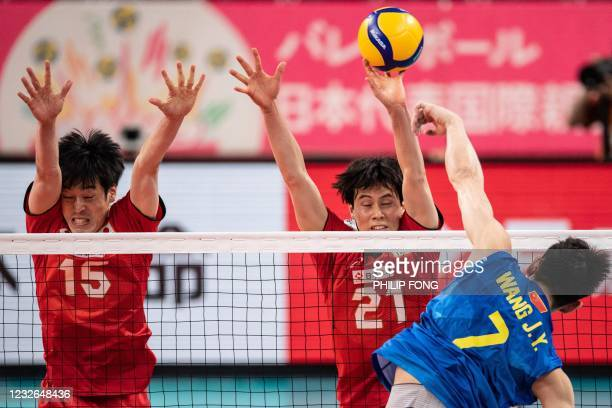 Japan's Ran Takahashi and Haku Ri try to block the ball from China's Wang Jingyi during the International Volleyball Games' Tokyo Challenge 2021...