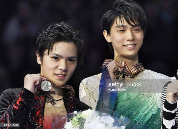 Japan's reigning men's figure skating Olympic champion Yuzuru Hanyu is pictured in a file photo smiling on the podium next to compatriot Shoma Uno...