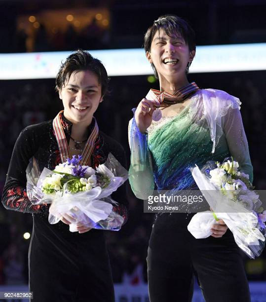Japan's reigning men's figure skating Olympic champion Yuzuru Hanyu is pictured smiling on the podium next to compatriot Shoma Uno after winning the...