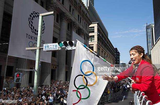 Japan's Rio de Janeiro Olympic team captain Saori Yoshida waves the Olympic flag from the top of a double decker bus as it passes through the...