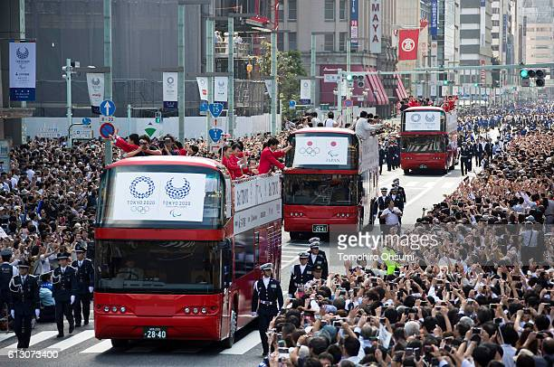 Japan's Rio de Janeiro Olympic team members wave from the top of double decker buses as they pass through the Nihonbashi area during the Rio Olympics...