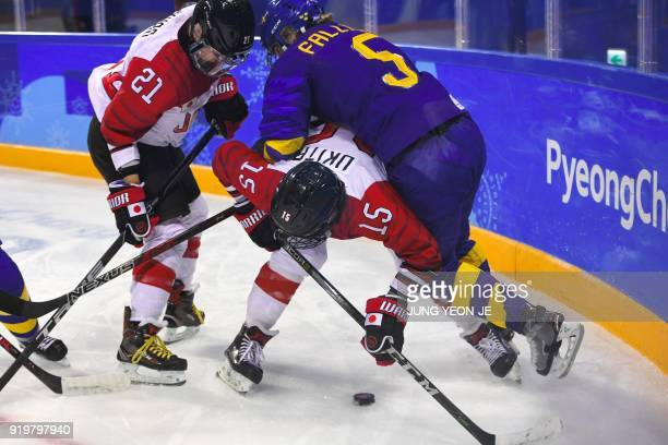 TOPSHOT Japan's Rui Ukita and Hanae Kubo fight for the puck with Sweden's Johanna Fallman in the women's classifications ice hockey match between...