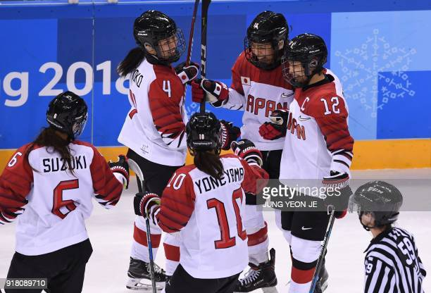 TOPSHOT Japan's Rui Ukita celebrates with teammates after a goal in the women's preliminary round ice hockey match between Japan and the Unified...